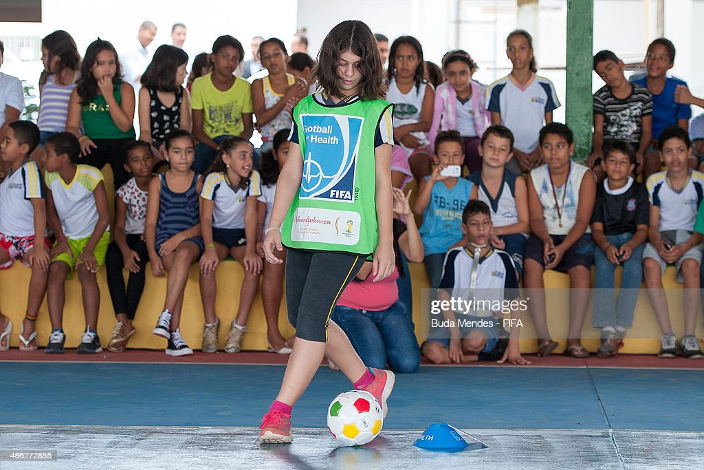 A kid kicks the ball during visit a FIFA 11 for Health Program as part of the 2014 FIFA World Cup Host City Tour on April 23, 2014 in Cuiaba, Brazil