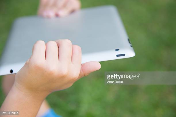 Kid laying on the backyard house watching cartoons holding iPad tablet with hands