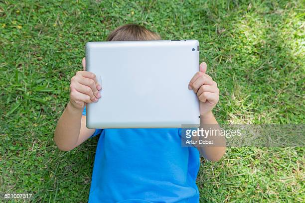 Kid laying on the backyard house watching cartoons with iPad tablet with view from above