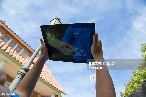 Kid laying on the backyard house watching cartoons with iPad tablet with blue sky
