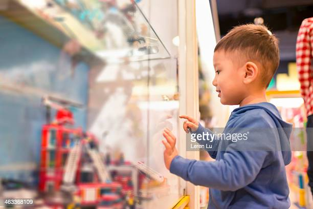 Kid looking and pointing at toys