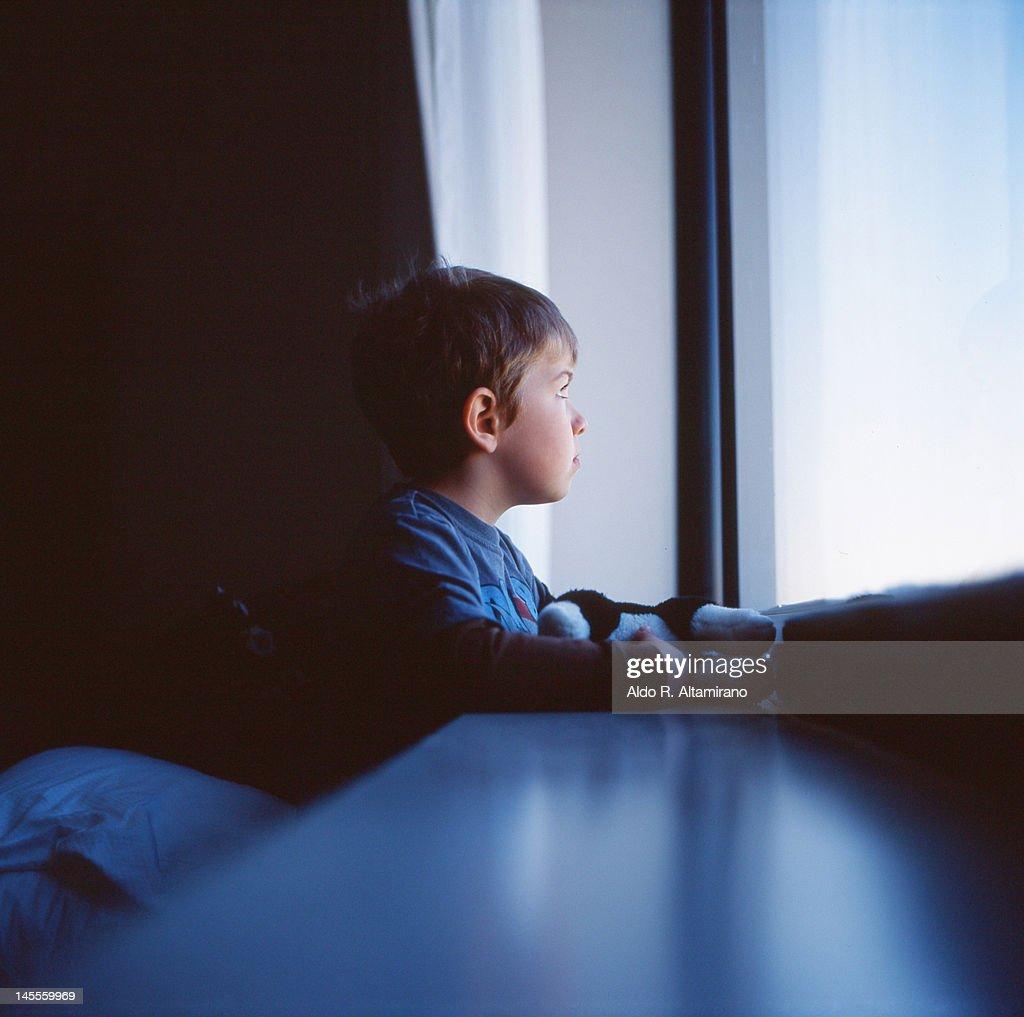 Kid looking at window : Stock Photo
