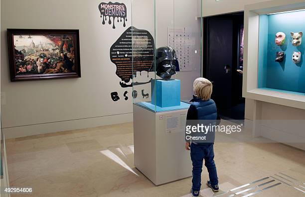 A kid looks at a mask of the Star Wars character Darth Vader during the exhibition 'Mythes Fondateurs D'Hercule a Dark Vador' at Petite Galerie du...