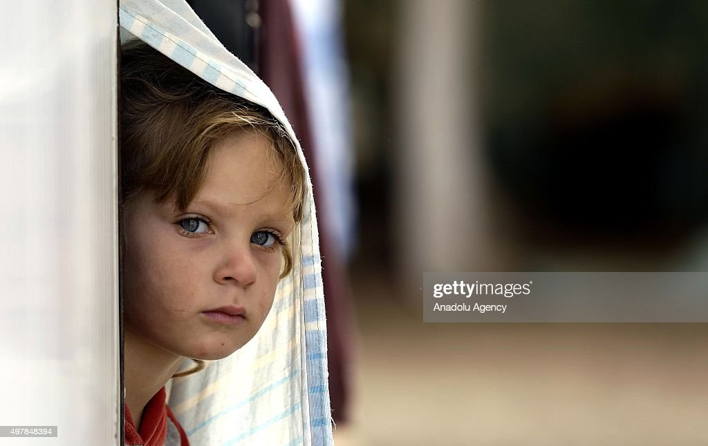 A kid looks out through their tent at the Beqaa Valley refugee camp in Beirut Lebanon on November 19 2015