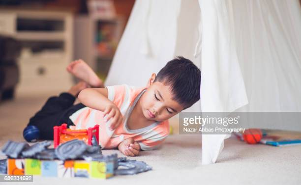 Kid lying Next To Tent And Playing With Toys.