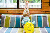 Kid holding Emoji face balloons and playing at home, in Auckland, New Zealand.