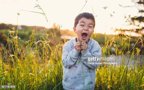 Kid making funny faces outdoor in lush meadow.
