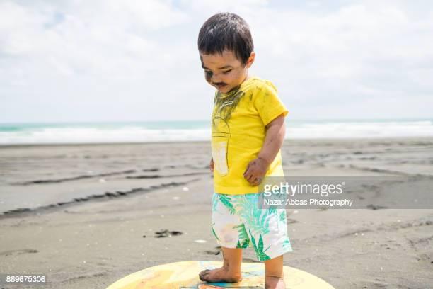 Kid on beach standing on sandboard.