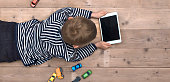 Top view header image with child laying down on the floor watching a movie on his tablet instead of playing with his toy cars