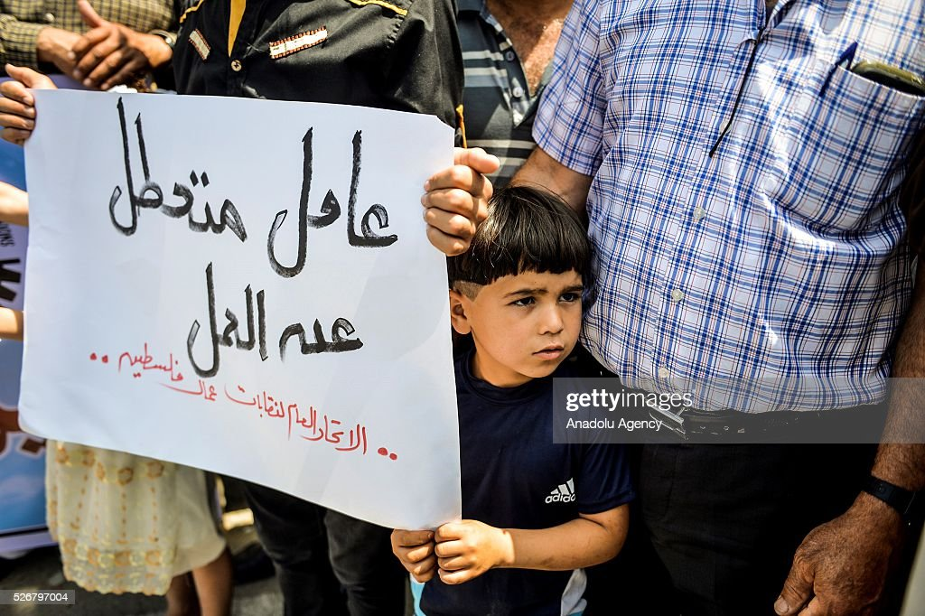 A kid participates a demonstration, demanding better working conditions for labors within May Day, International Workers' Day, celebrations in front of government building in Gaza City, Gaza on May 01, 2016.