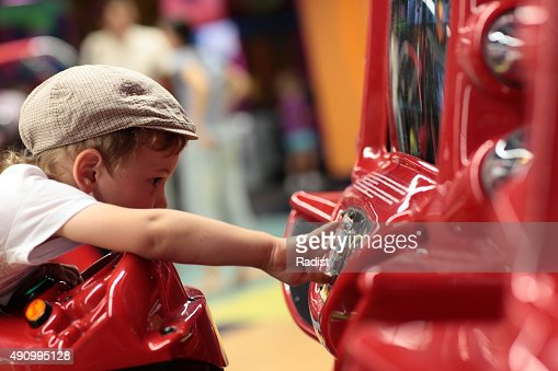 Kid playing arcade game machine : Stock Photo