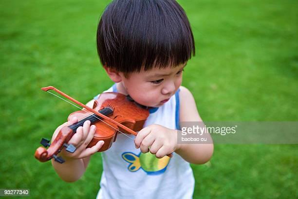 kid playing toy violin