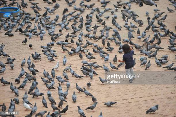 A kid playing with the pigeons at the premises of Boudhanath Stupa Kathmandu Nepal on Tuesday July 11 2017 Boudhanath Stupa is listed as a UNESCO...
