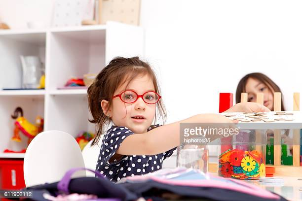 Kid playing with toys in kindergarten room