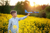 Child plays with a toy airplane in the sunset and dreams of journey in summer day.
