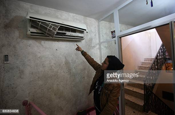 A kid points to a broken air conditioning after Israeli soldiers raid several houses at Balata Refugee Camp in Nablus West Bank on January 3 2017 No...