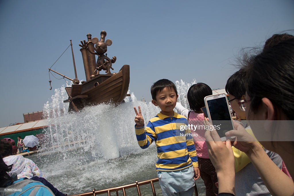 Kid poses as his mother takes picture in front of a fountain outside Disneland Shanghai in Pudong District in Shanghai, China, Apr. 30 2016. Disneyland Shanghai still under costruction and has planned to open on June 16, 2016.