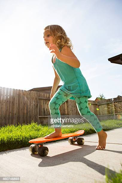 Kid riding a skateboard outside.