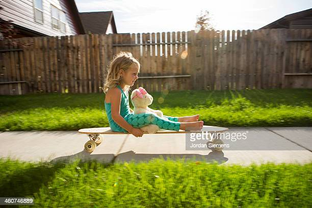 Kid riding on skateboard outside.
