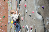 little active boy rock climbing at indoor gym