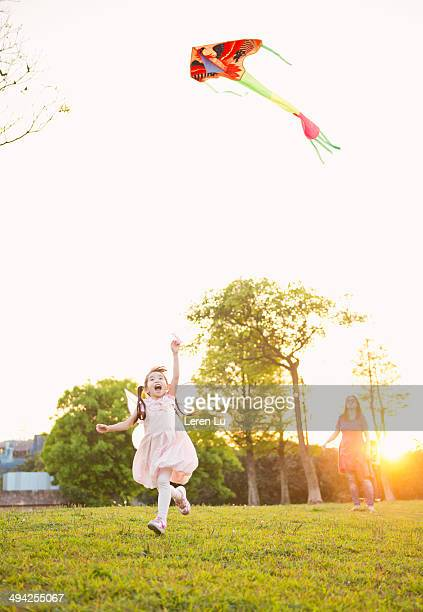 Kid running and flying kite on grass
