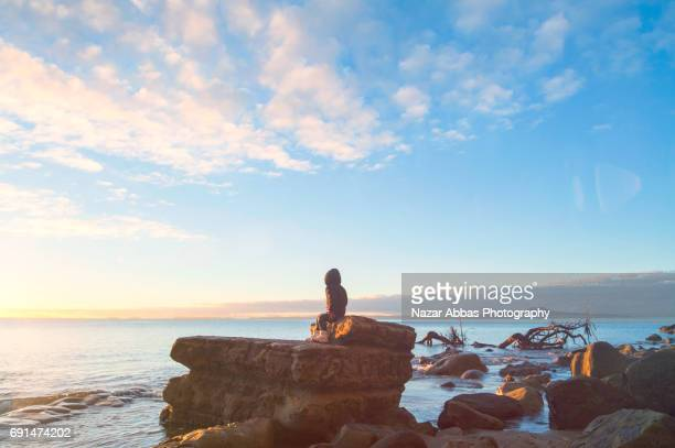 Kid Sitting On Rock And Looking Towards Sunrise With Rangitoto Island In Background.