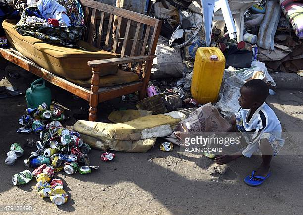 A kid smashes cans before recycling in the streets of Cotonou on July 1 2015 French president Francois Hollande is expected tonight for a state visit...