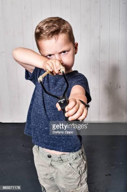 Kid takes aim with a slingshot