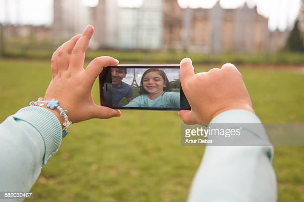 Kid taking selfie with smartphone in Paris.