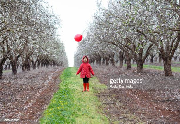 Kid throwing red balloon on almond field.