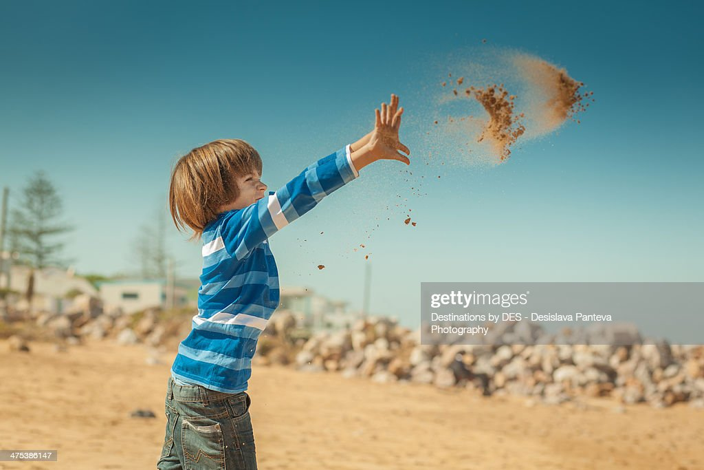 Kid throwing sand on the beach