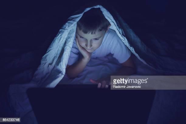 暗い部屋でノート パソコンを使用しての子供