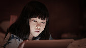 Cute asian kid girl using tablet, in darkness room at home, bright screen light reflex on her face. Concepts of learning internet at home.