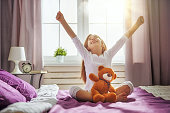 A nice child girl enjoys sunny morning. Good time at home. Kid wakes up from sleep.