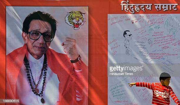Kid walking past a signboard wishing Balasaheb Thackeray on his 84th birthday at Shivaji Park Dadar on January 23 2011 in Mumbai India