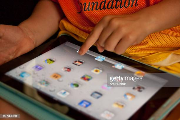 Kid with IPad touching screen and interact with technology at home