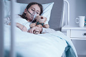 Kid with cystic fibrosis lying in hospital bed with oxygen mask and plush toy