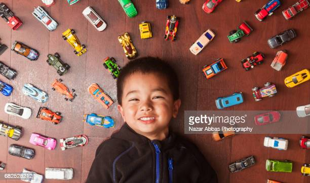 Kid with Playful Smile Lying On Floor With Cars Around Him.