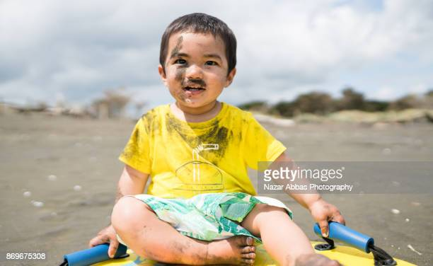 Kid with sand on his face sitting on sandboard.