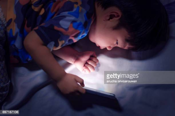 kid with tablet in the dark on bed and reading at Night .
