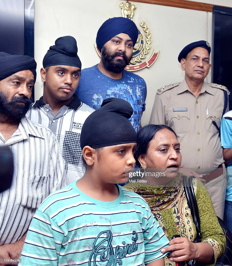A kidnapped boy, rescued by Delhi police with his family members at Delhi Police head quarters in New Delhi on Sunday.