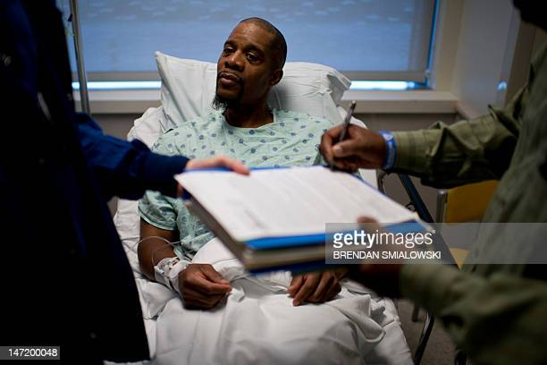 A kidney donor watches as a consent form is singed by a witness before a kidney transplant operation at Johns Hopkins Hospital June 26 2012 in...