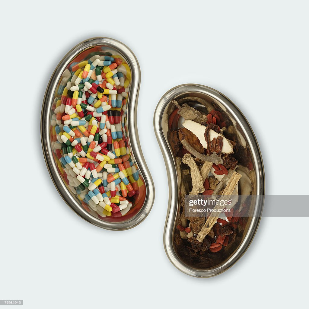 A kidney shaped bowl of pills beside a bowl of herbs : Stock Photo