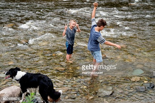 Kids and dog playing in river wetting their clothes. : Stock Photo