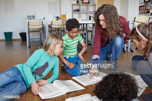 Kids are taught math on the floor by teacher : Stock Photo