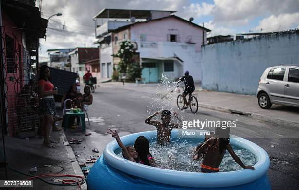 Kids bathe in a pool on the street on January 28 2016 in Recife Pernambuco state Brazil Health officials believe as many as 100000 people have been...