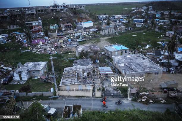 Kids bike in an area without grid power or running water about two weeks after Hurricane Maria swept through the island on October 5 2017 in San...