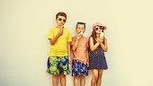 Kids eating gelato and soft serve ice cream. Boys and little girl in sunglasses enjoying summer holidays vacation. Instagram filter.