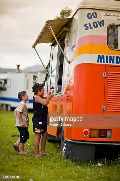 Kids buying ice-cream at an ice-cream van.