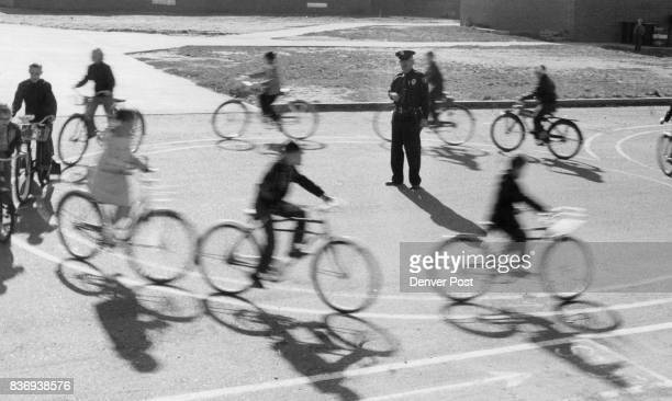 Kids Carefully Wheel Around Figure Eights Making sure they stay within the two food wide painted stripes Officer Henry R Putnam safety education...
